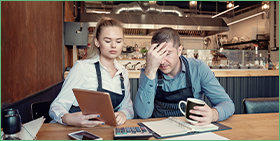 Coface Focus - the business insolvency paradox in Europe: miracle and mirage. The photo shows a man and a woman in a café worried about their corporate finances.