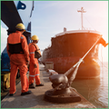 Coface: United States Country Risk Focus. The photo shows two men in high viz protective equipment standing by a ship in a harbour.